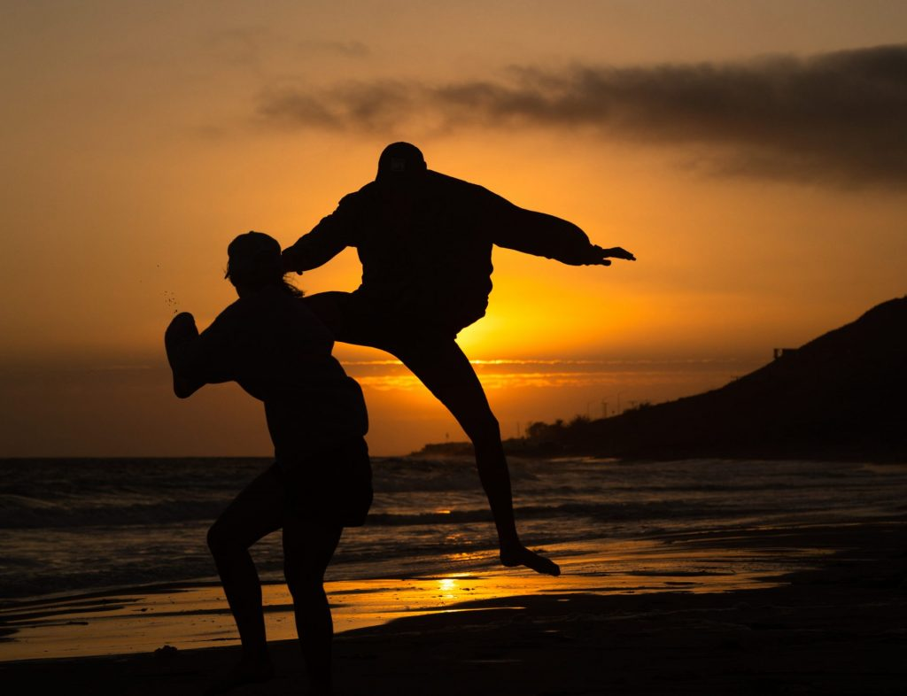 Silhouettes of two people jumping on the beach at sunset.
