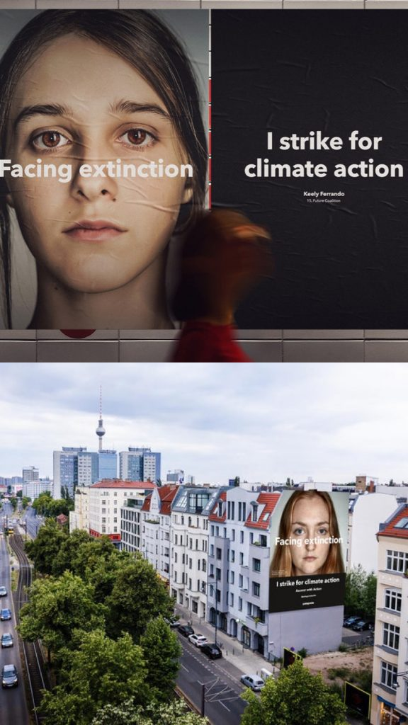 "Street view of building advertisements which say: ""Facing extinction"" and ""I strike for climate action."""