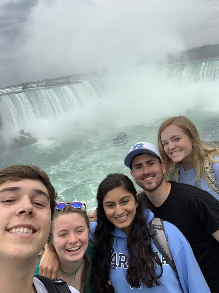 The group of scholars pose with the Niagara Falls in the background.
