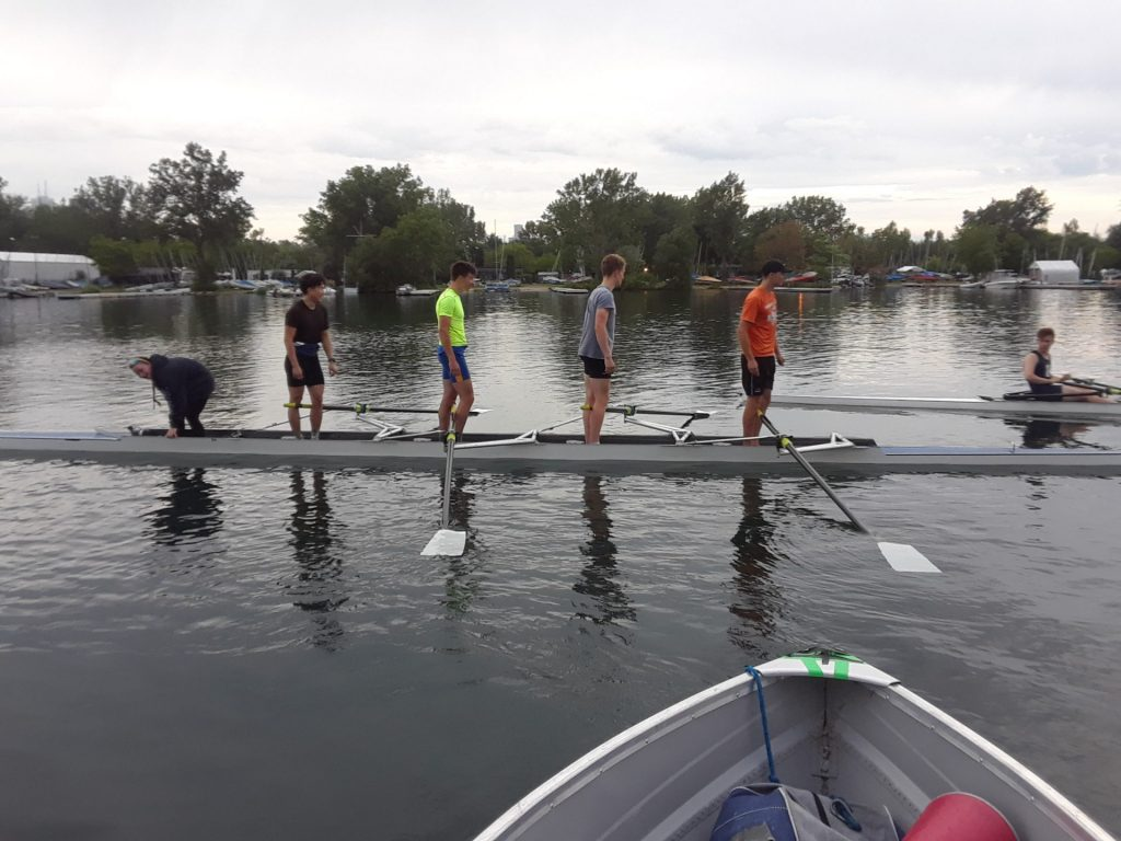 Four people stand on rowing boat, preparing to set off for their practice.