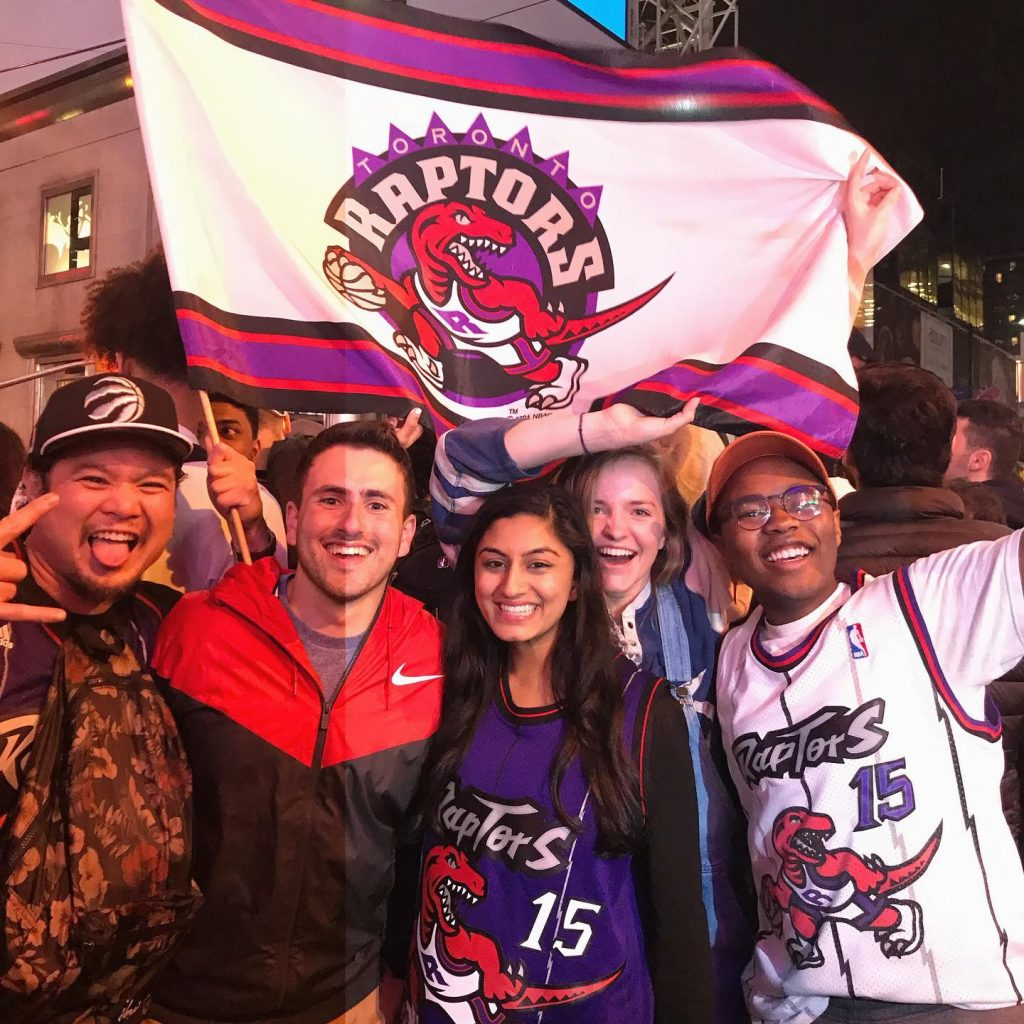 Group shot of five people holding a Toronto Raptors flag after the championship game.