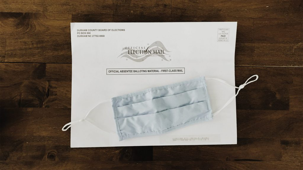 An absentee ballot envelop sits on a wooden table with a cloth face mask on top