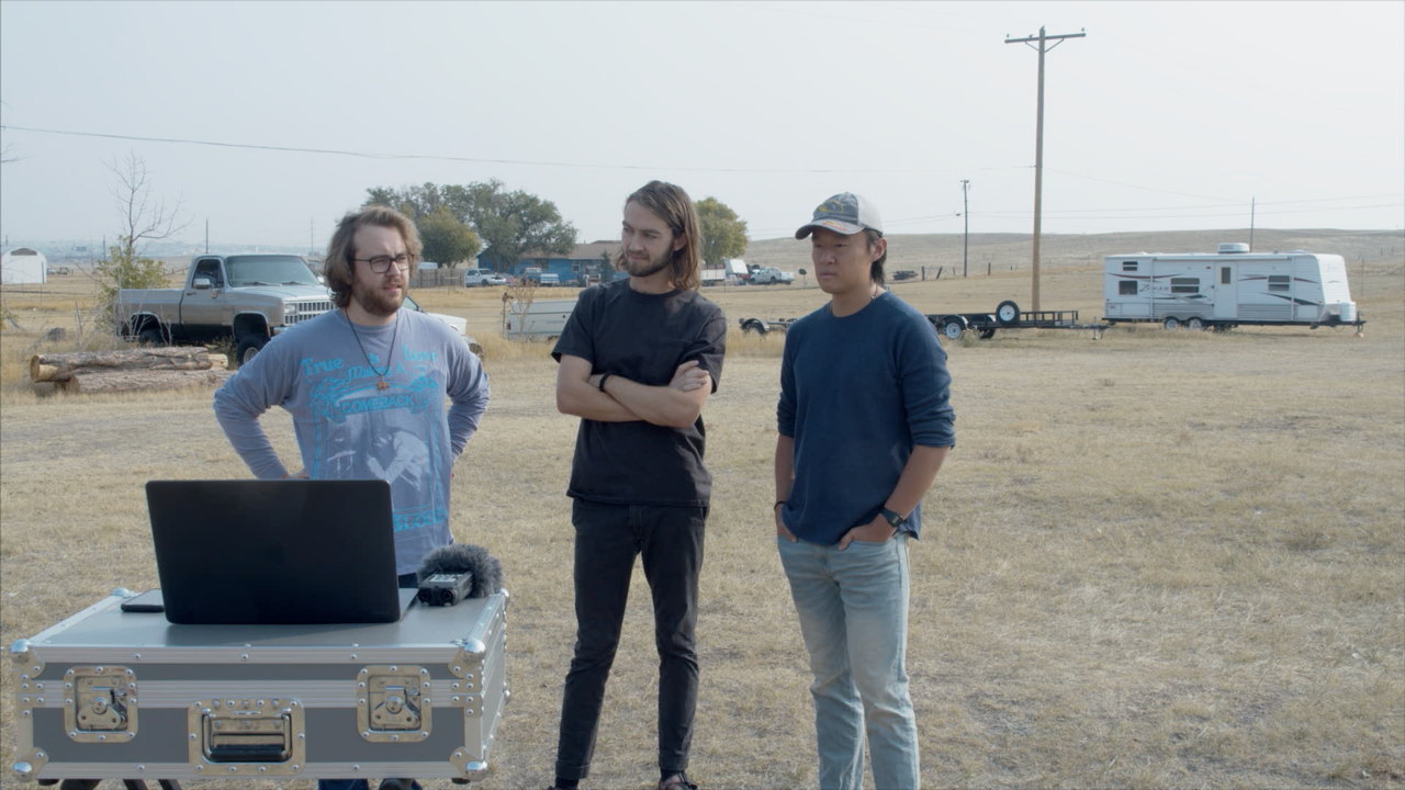 Sam, Nicholas, and Eric stand outside behind a laptop with a field behind them.