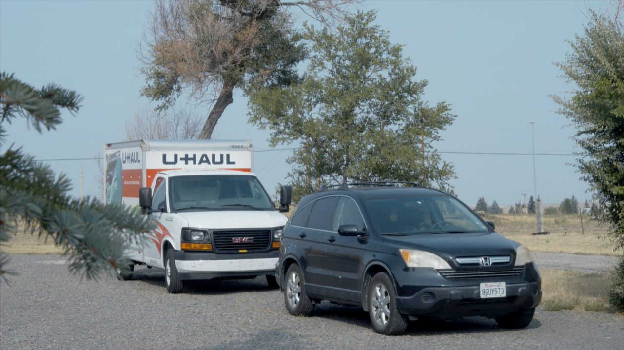A U-Haul van and a car parked with trees in the background.