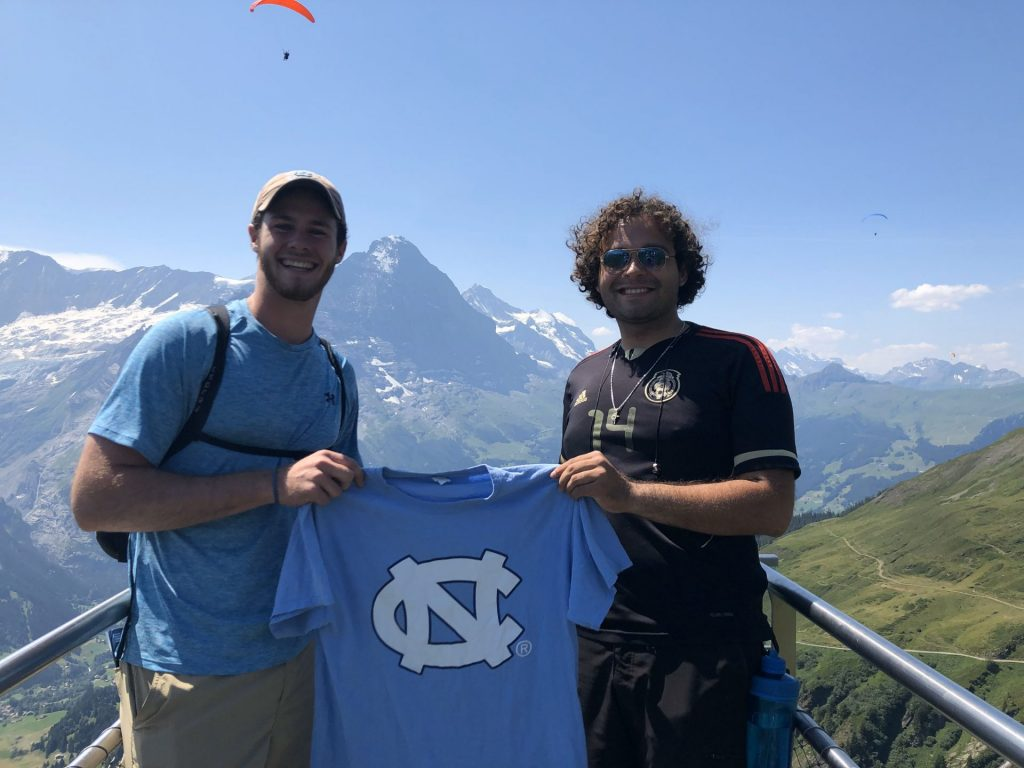 Two scholars hold up a UNC Tar Heels t-shirt outside with the alps in the background.