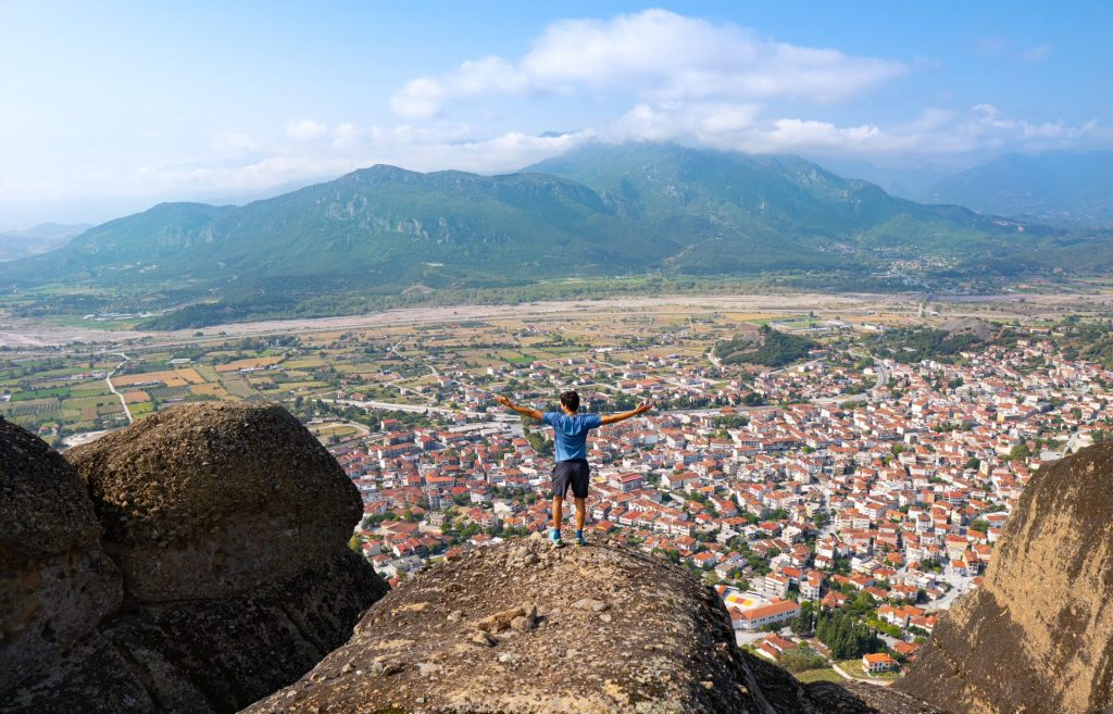 A person stands, with arms extended, looking out over a city bordered by mountains.