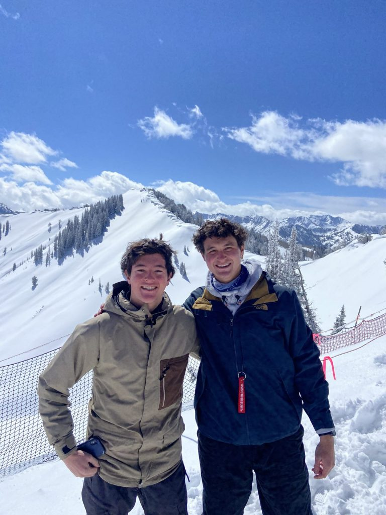 Two skiers stand outside with snow-capped mountains behind them.