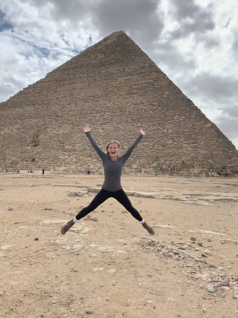 A person jumps in the air with a pyramid in the background.