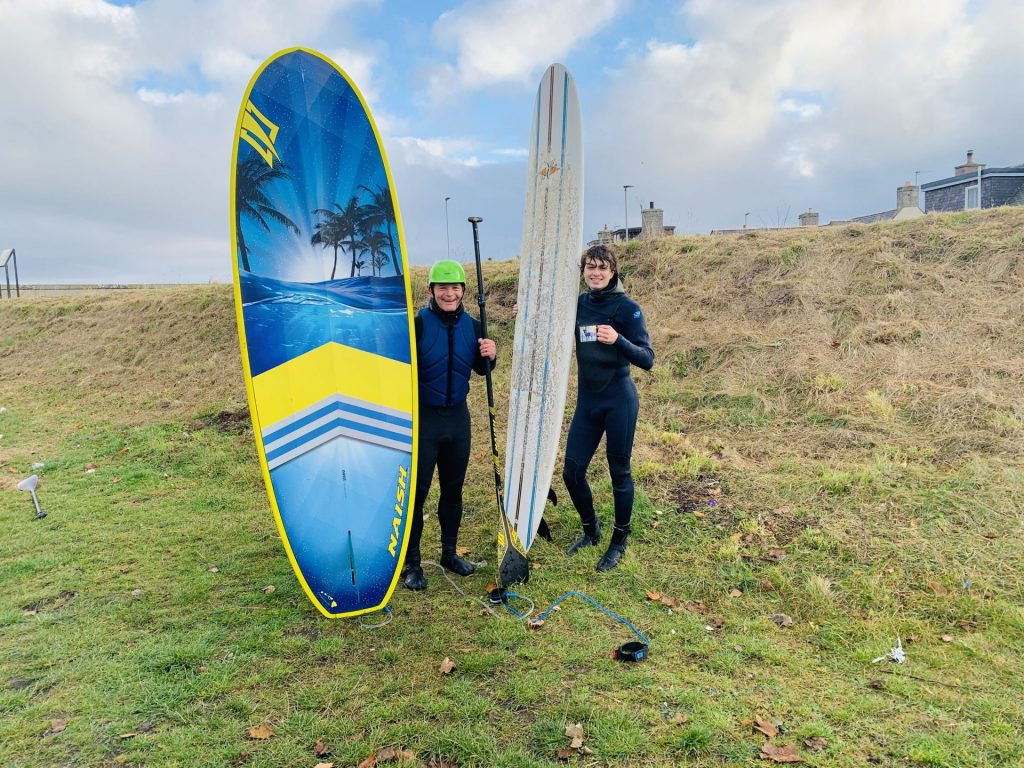 Two people hold surfboards upright, standing on grass near the seacoast.