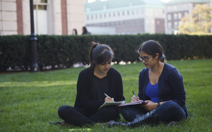 """A Matriculate """"Advising Fellow"""" mentors a student while sitting outside on the grass."""