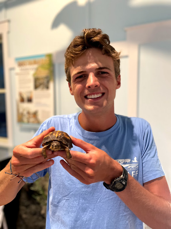 Michael holds a small turtle.