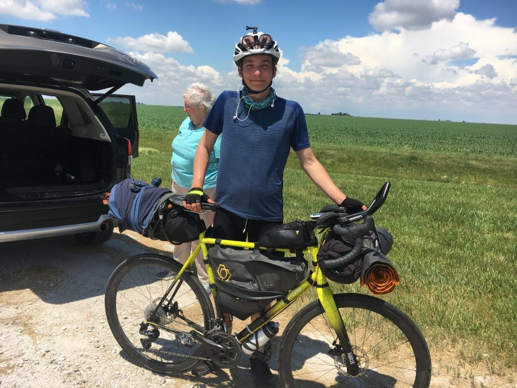 Emmaus smiles while standing behind his bike on a dirt road besides a grassy field.