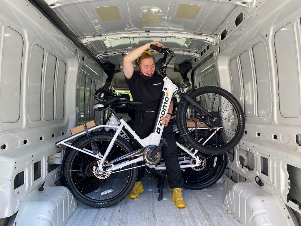 Megan holds up a Zoomo bike inside of a large supplies van.