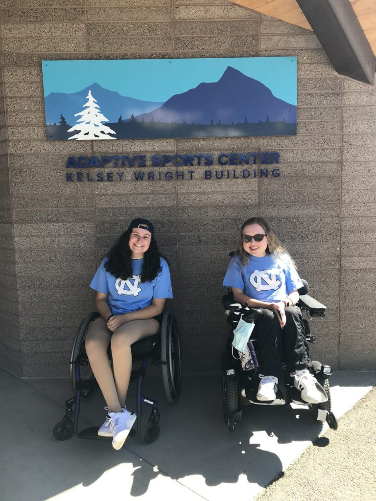 Laura and Eleanor smile in front of the Adaptive Sports Center building wearing Carolina t-shirts.
